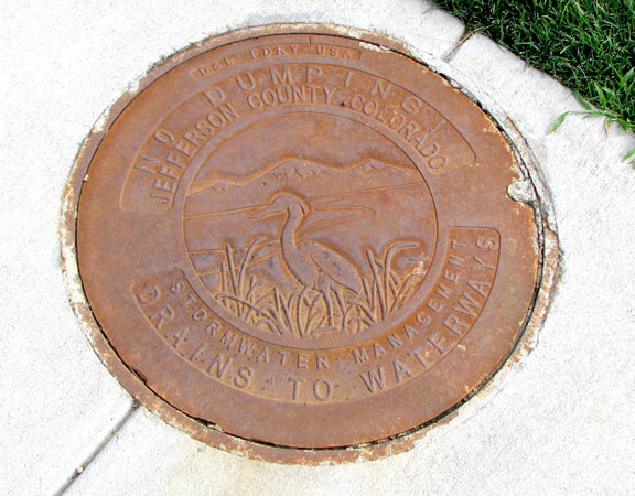 A sign on the manhole cover designates a sensitive watershed area.
