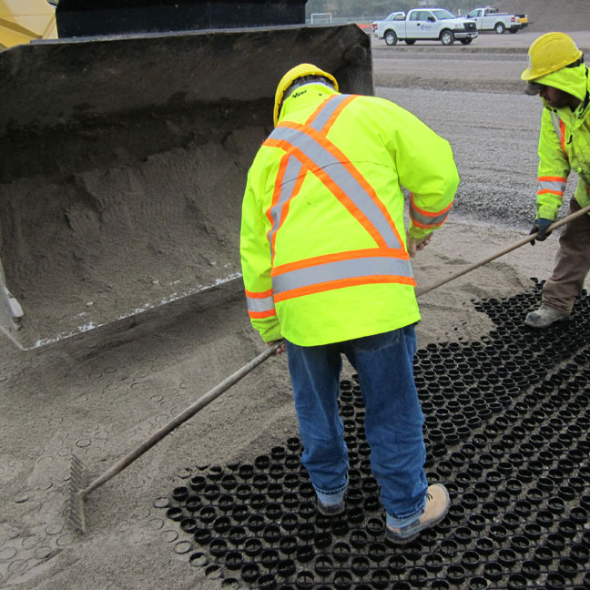 Workers move the sand into the Grasspave2 grass porous paver.