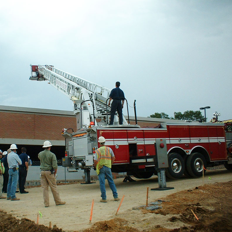The ladder is extended with the outriggers engaged.